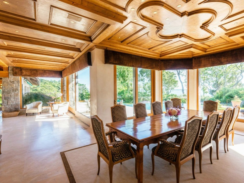 theres-also-another-room-with-an-eight-seat-dining-room-table-under-an-elaborate-wood-work-ceiling